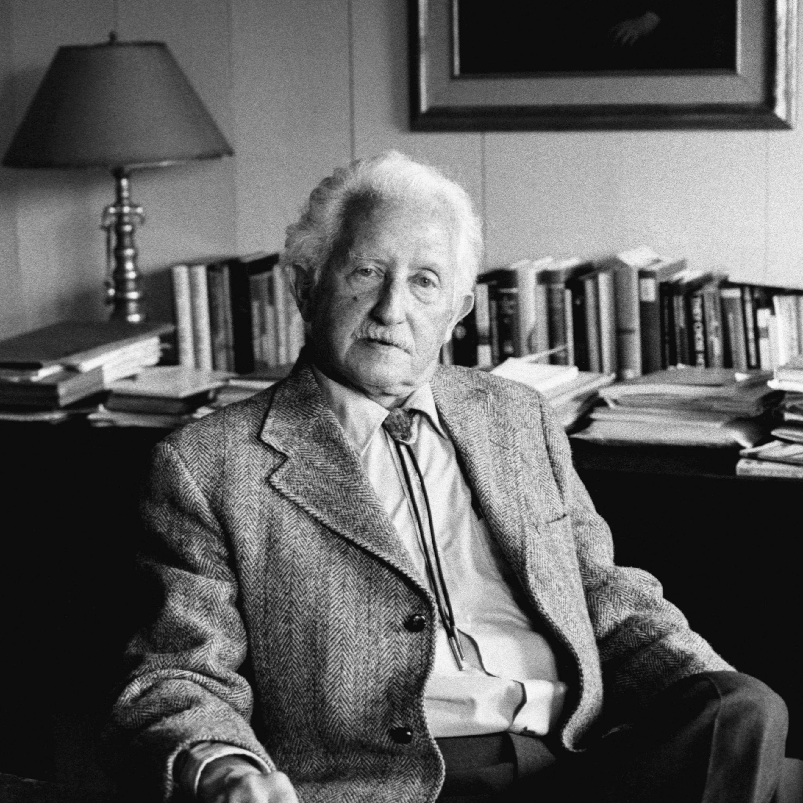 Psychologist Erik Erikson sitting at a desk