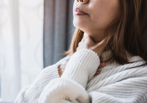 Woman holding her neck as if she is having trouble swallowing