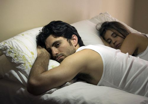 Couple in bed at night, woman sleeping, man awake