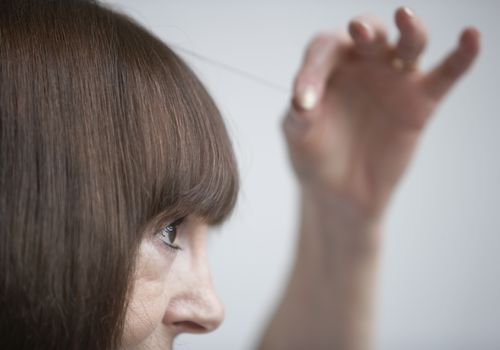 Woman pulling out a strand of her hair