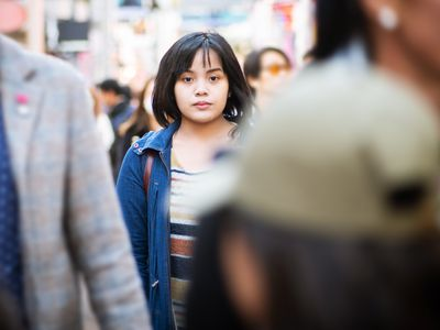 young woman walking in the middle of a busy sidewalk
