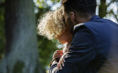 A parent and child embracing in the woods