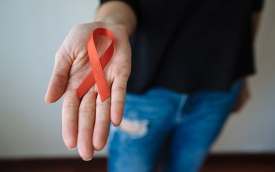 Woman holds red AIDS support ribbon.