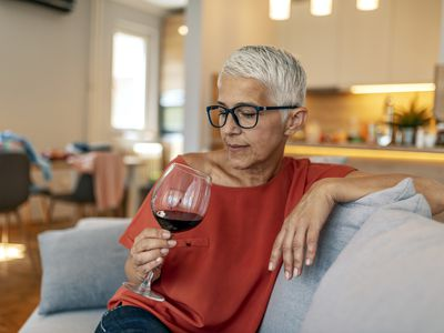 Mature woman sitting on the couch with a glass of wine