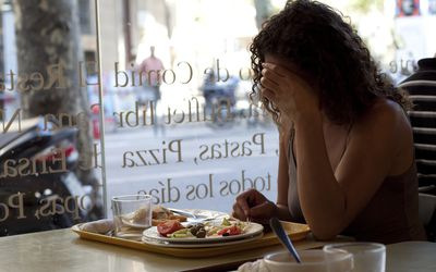 sad woman eating alone in cafe