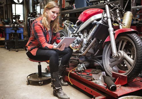 Woman looking at tablet next to motorcycle in garage