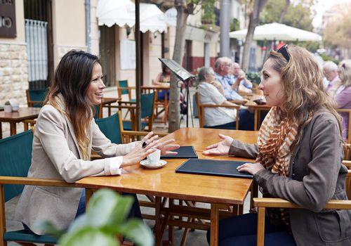 Two women sitting outside café