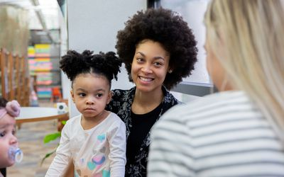 Beautiful young mother and her toddler daughter meet with friends during support or play therapy group