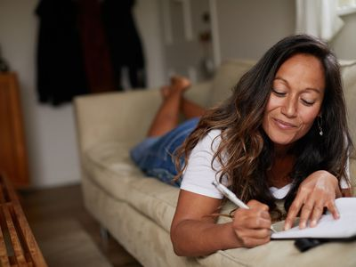 Woman journaling on the couch