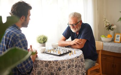 Elderly father concentrate to playing Chess game with Son
