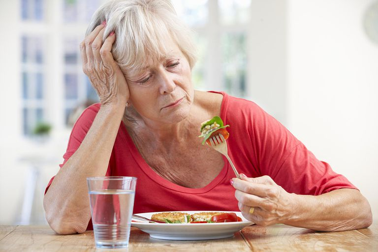 Older woman trying to eat; loss of appetite