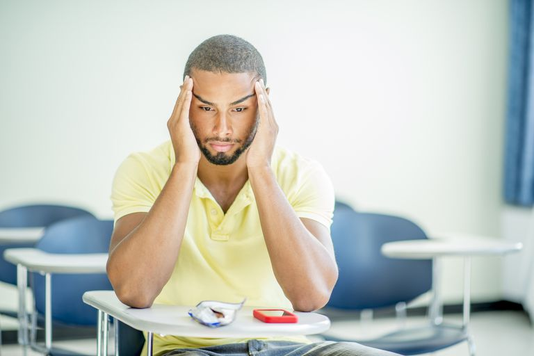 male college student with hands on his head, sitting at desk in classroom