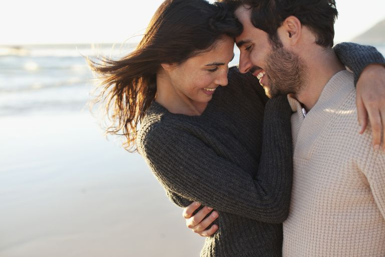 man and woman hugging and smiling on a beach