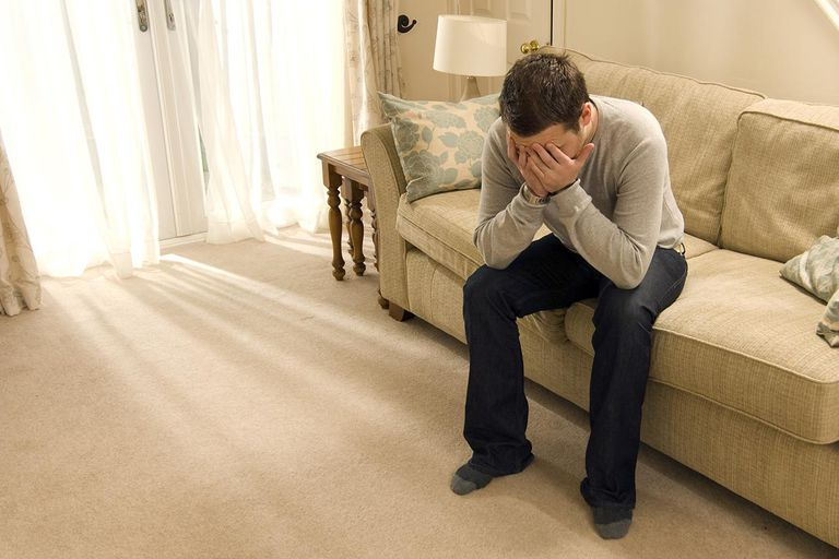 upset young man with face in hands sitting on couch