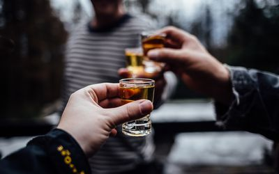 Close-Up Of Hands Holding Alcoholic Drinks