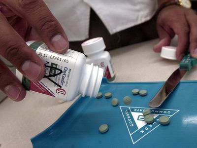 Bottle of OxyContin being poured by pharmacist