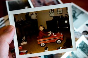 A close-up of a vintage photo that shows a young bow riding in a child-size red car.