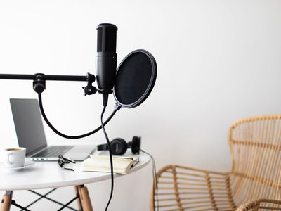 Audio studio with laptop, microphone with pop filter and headphones on white table