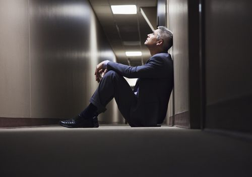 Man sitting on the ground, looking up