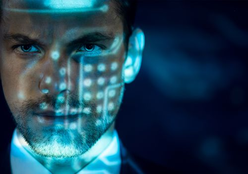 Man wearing a suit has blue light projecting dots and lines on his face