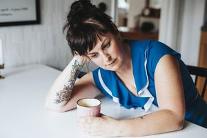 woman-looking-depressed-while-holding-a-cup-of-coffee