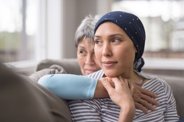 older woman embracing younger woman by a window