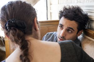 man and woman having serious talk in restaurant booth