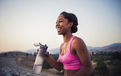 Happy female runner holding water bottle