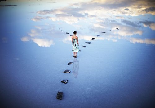 Woman in surreal landscape that looks like she's walking on clouds
