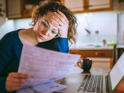 Woman looking stressed reading bills