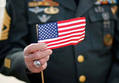Veteran holding small American flag