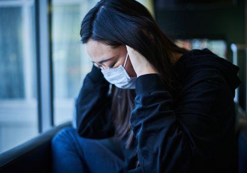 sad woman wearing a mask