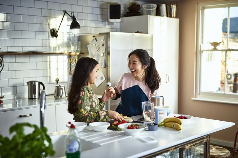 Woman holding yogurt on spoon towards girl, laughing, threatening to smear food on daughter's face, messing about, having fun, playing, bonding