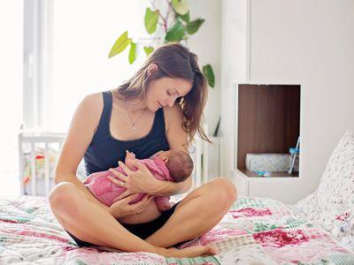 Mom breastfeeding on a bed