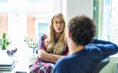 woman with folded arms having a serious talk with a man