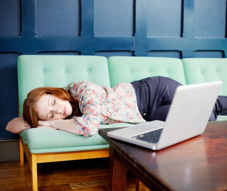 Woman asleep on sofa next to laptop on coffee table
