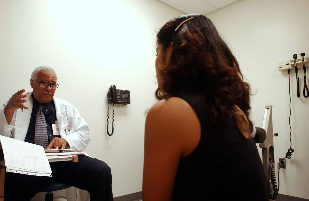 Woman speaking with doctor in exam room