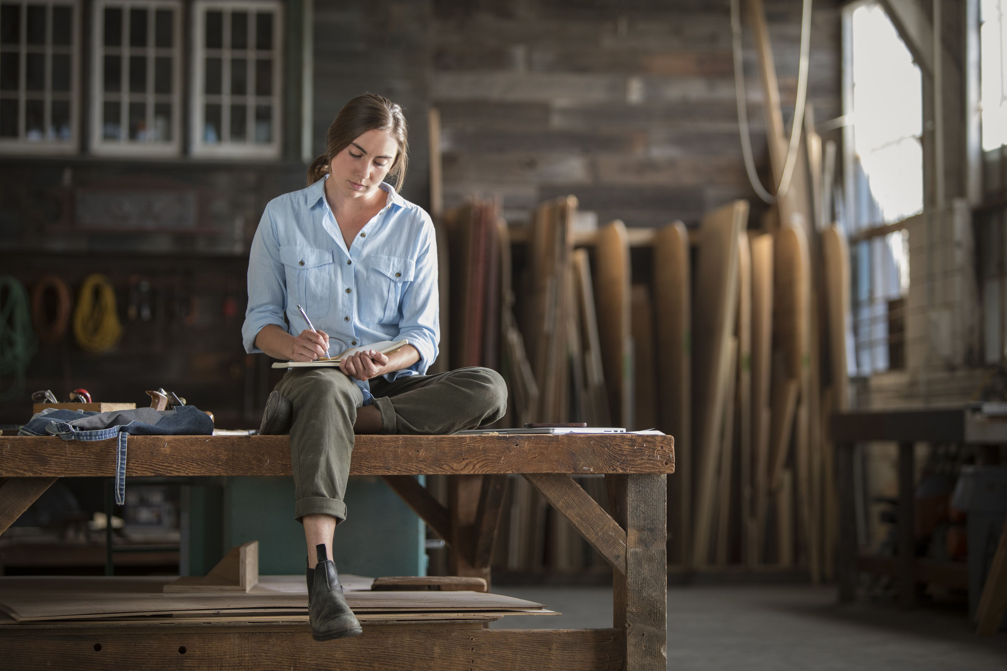 Young Woman Entrepreneur in Her Element Sits on Workbench in Lofty Maker Space, Calculating the Day's Design Challenges