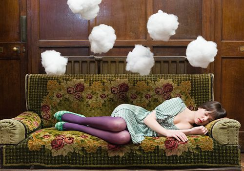 woman napping on couch with clouds floating above her
