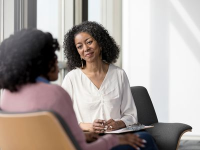 Mature counselor listens compassionately to unrecognizable female client