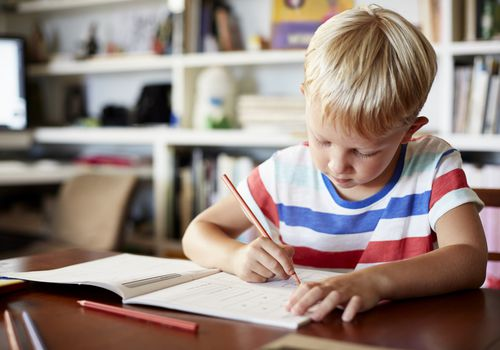 Young boy writing in workbook