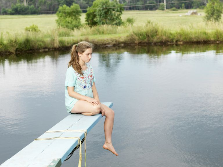 Unhappy girl sitting on a diving board over a pond