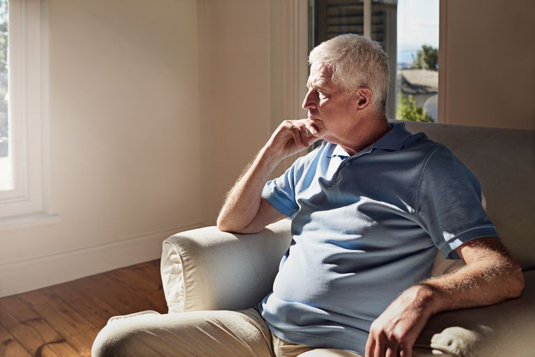 Senior man looking out window while sitting in chair