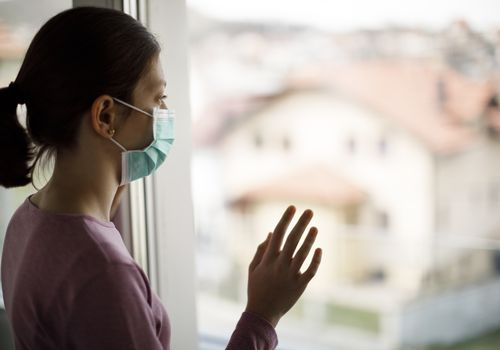 Woman wearing a face mask looking out window