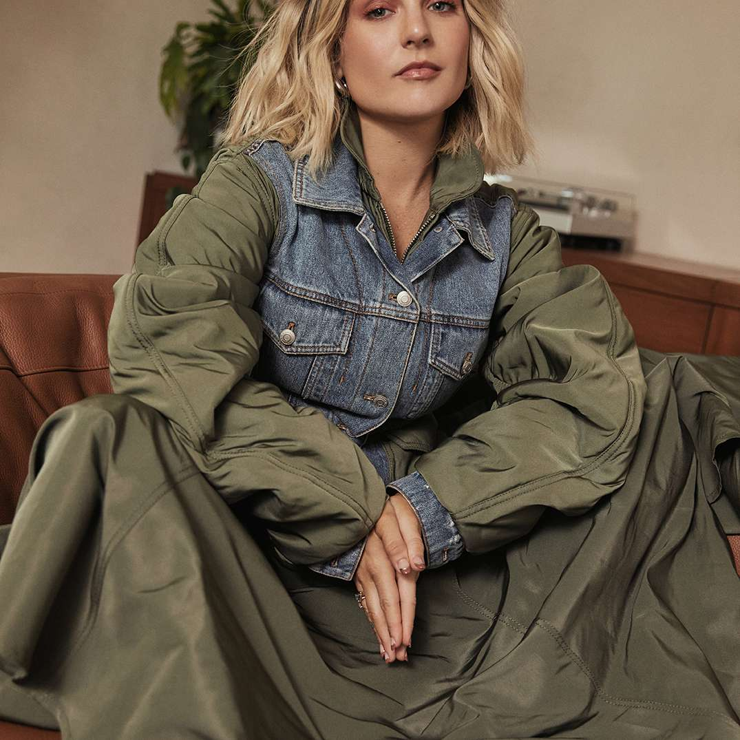 JoJo wearing a denim and nylon bomber jacket, sitting on her couch