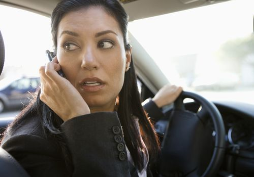 woman talking on cell phone while driving and looking over her shoulder
