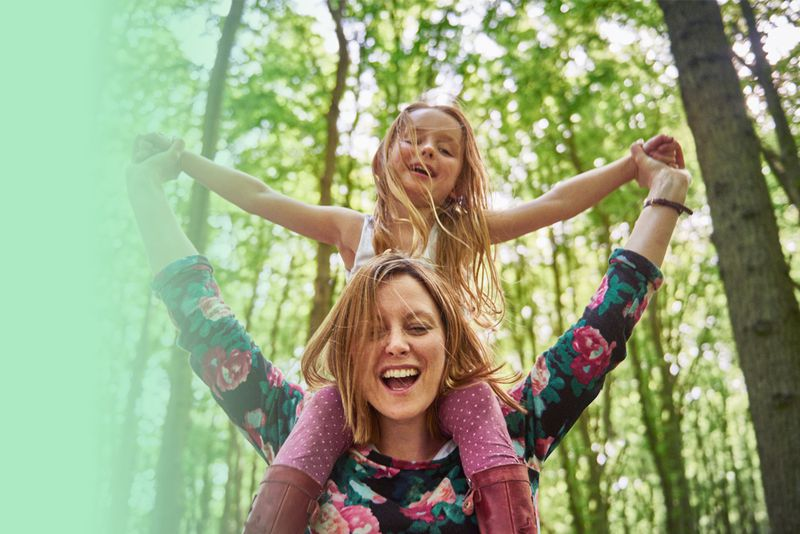 Daughter on mother's shoulders in the woods