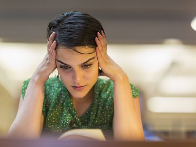 Female student with hands on her head studying in library
