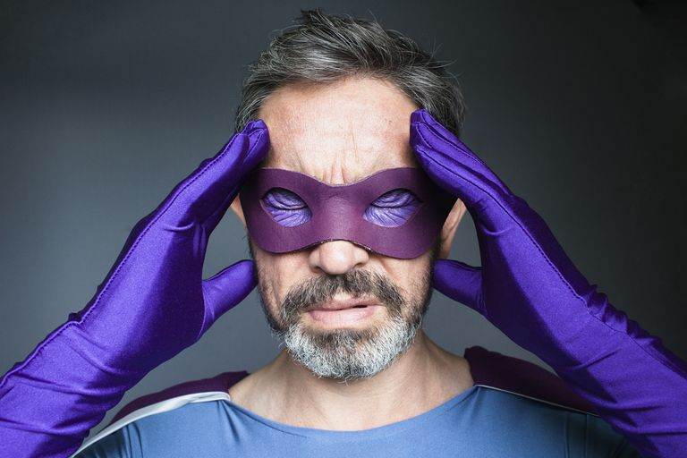 Close-up of superhero with headache against gray background