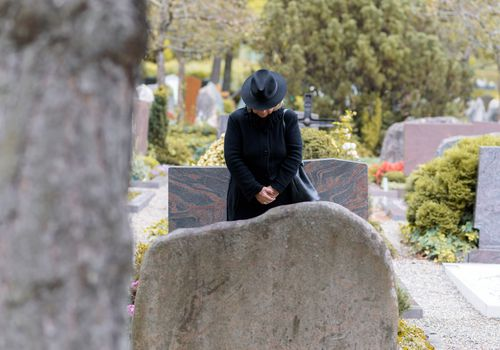 Woman dressed in black standing at a grave site